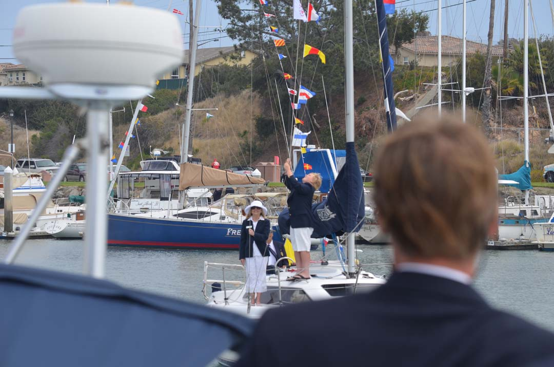 A crew aboard a sailboat prepares to salute Oceanside Yacht Club Commodore Karl Walker. Photo by Tony Cagala