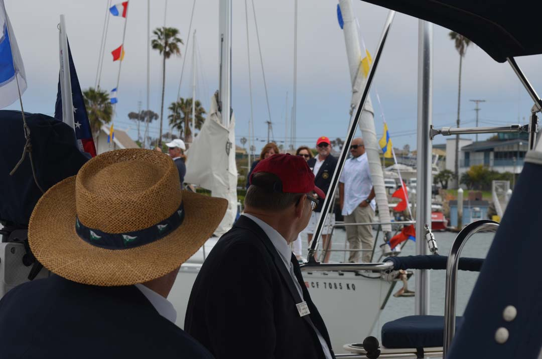 "A reviewing party from the Oceanside Yacht Club watches on as a sailboat approaches. The judges were scoring for several categories, including what's called ""dressed sail,"" where dress flags are used to adorn masts. Photo by Tony Cagala"