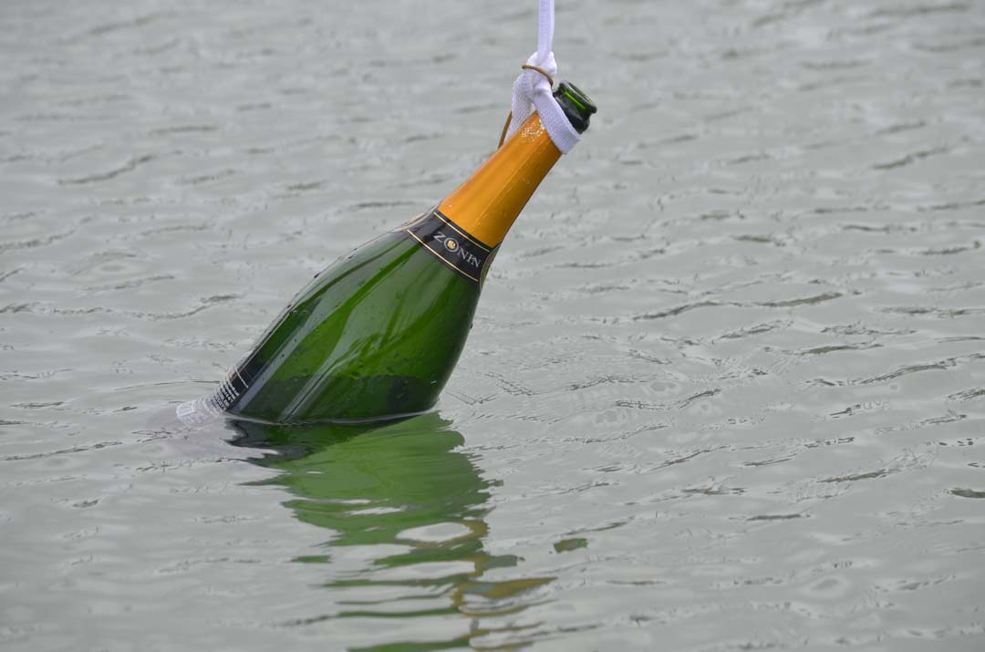 A champagne bottle is tied to the bow of one of the yachts. The bottle would be partly submerged while sailing to keep it cool for consumption later. Photo by Tony Cagala