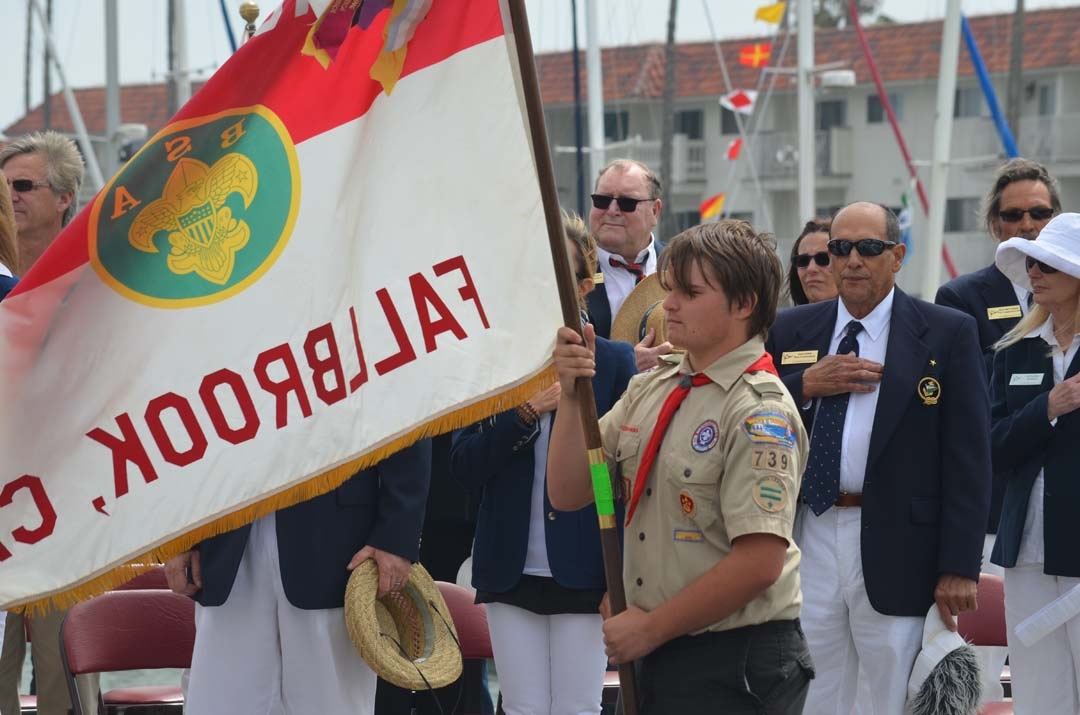 A flag carrier of the Boy Scout Troop 739 helps to present colors during the Oceanside Yacht Club's Opening Day ceremony. Photo by Tony Cagala