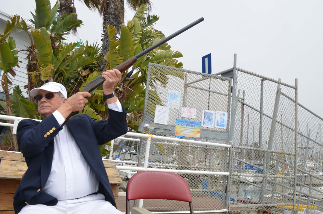 A member of the Oceanside Yacht Club fires blank ammunition after the introduction of dignitaries and visiting yacht club associations. Photo by Tony Cagala