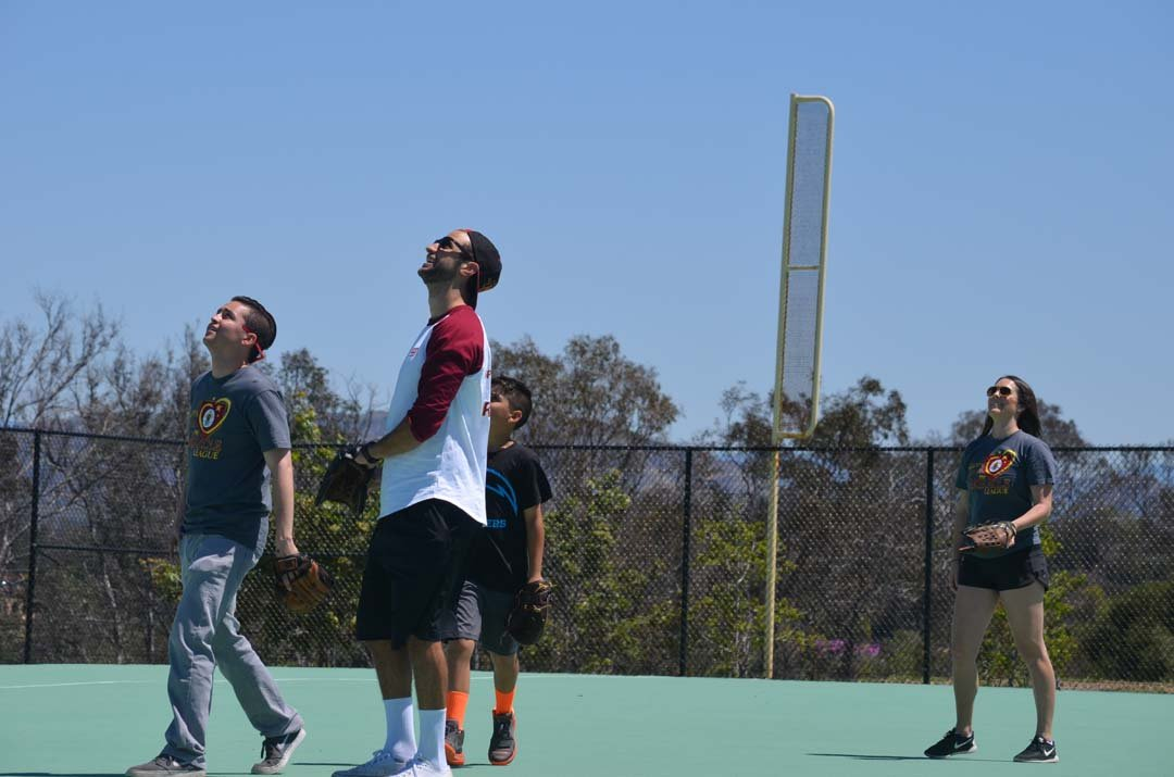 Members of San Diego State University fraternity Pike Kappa Alpha shag flyballs in the outfield during Saturday's 10th annual home run derby for the Miracle League of San Diego. Photo by Tony Cagala