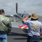 People stand behind the P-51 Mustang as it taxis to the runway. Photo by Tony Cagala