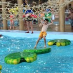 Jordan Barnhart of Carlsbad works his way across Big Foot Pass on moving lily pads, one of the challenging elements at Great Wolf Lodge waterpark in Garden Grove. Photo by E'Louise Ondash