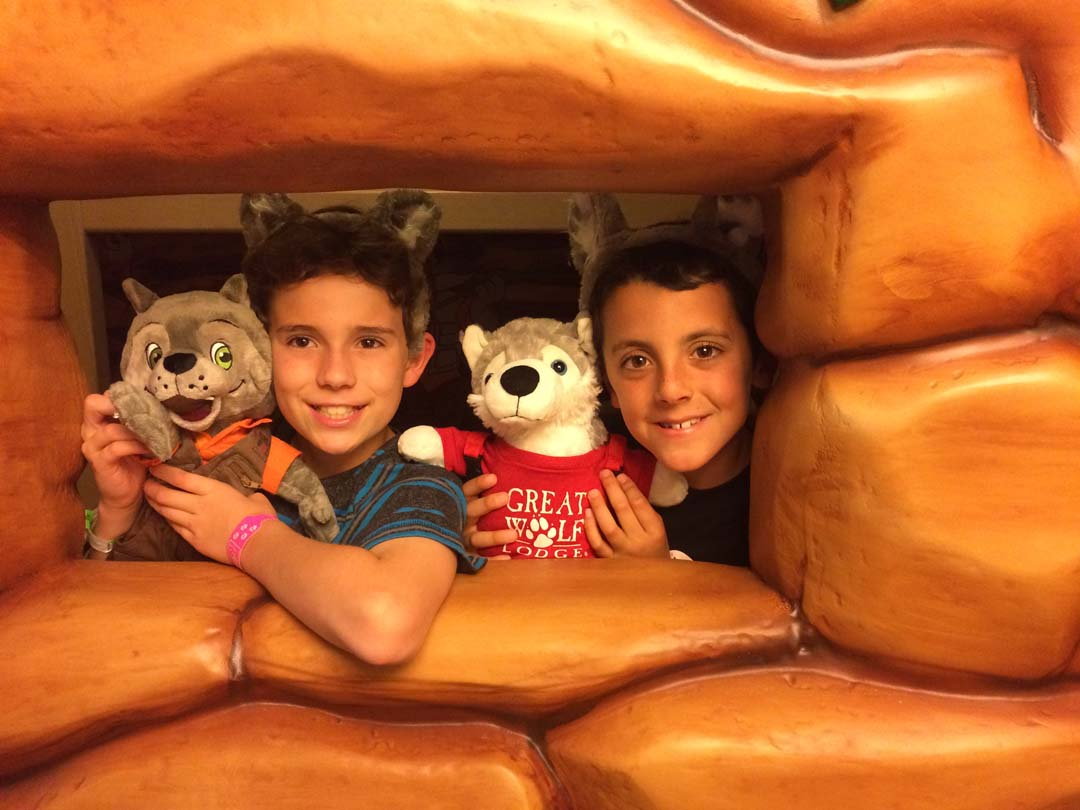 """David Ondash, left, and Jordan Barnhart, both of Carlsbad, peer out from their wolf-den window, a kid-space in the hotel suite separated by faux rock walls. The """"den"""" is furnished with bunkbeds and television, and three-dimensional artwork that can be animated with a MagiQuest wand. Photo by E'Louise Ondash"""