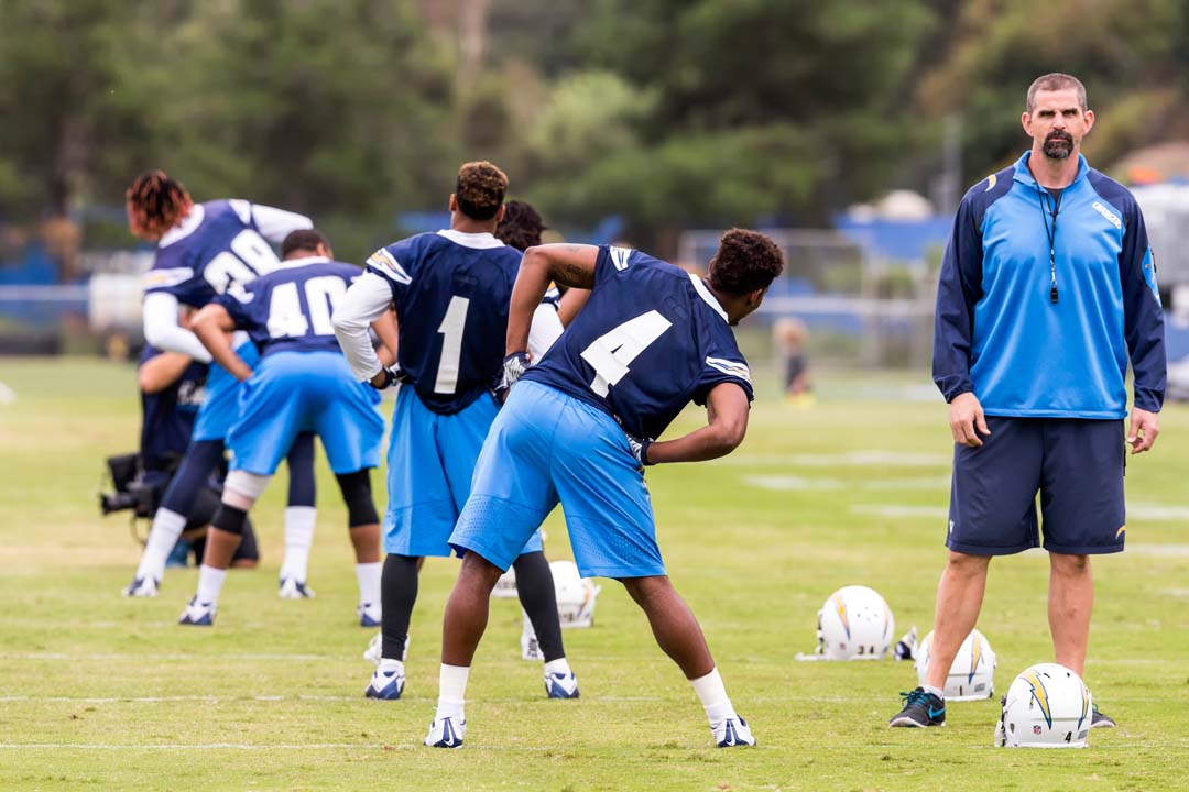 Rookies attending San Diego Chargers 2016 Rookie mini-camp take part in stretching activities under the watchful eye of one of the team's coaches. Photo by Bill Reilly