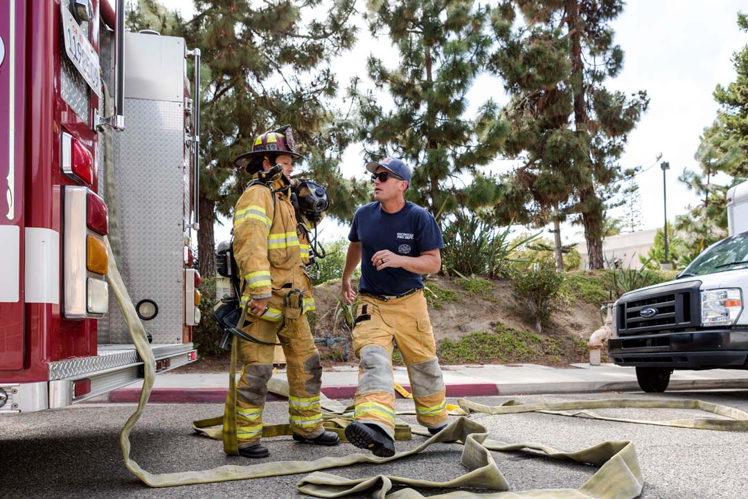 Encinitas firefighters pull hose and prepare to fight a fire that spread from a tree to the roof of several small businesses in an Encinitas shopping center. Photo by Bill Reilly