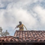 An Encinitas firefighter sprays water on a hot spot at 441 Encinitas Blvd. on Sunday. Photo by Bill Reilly