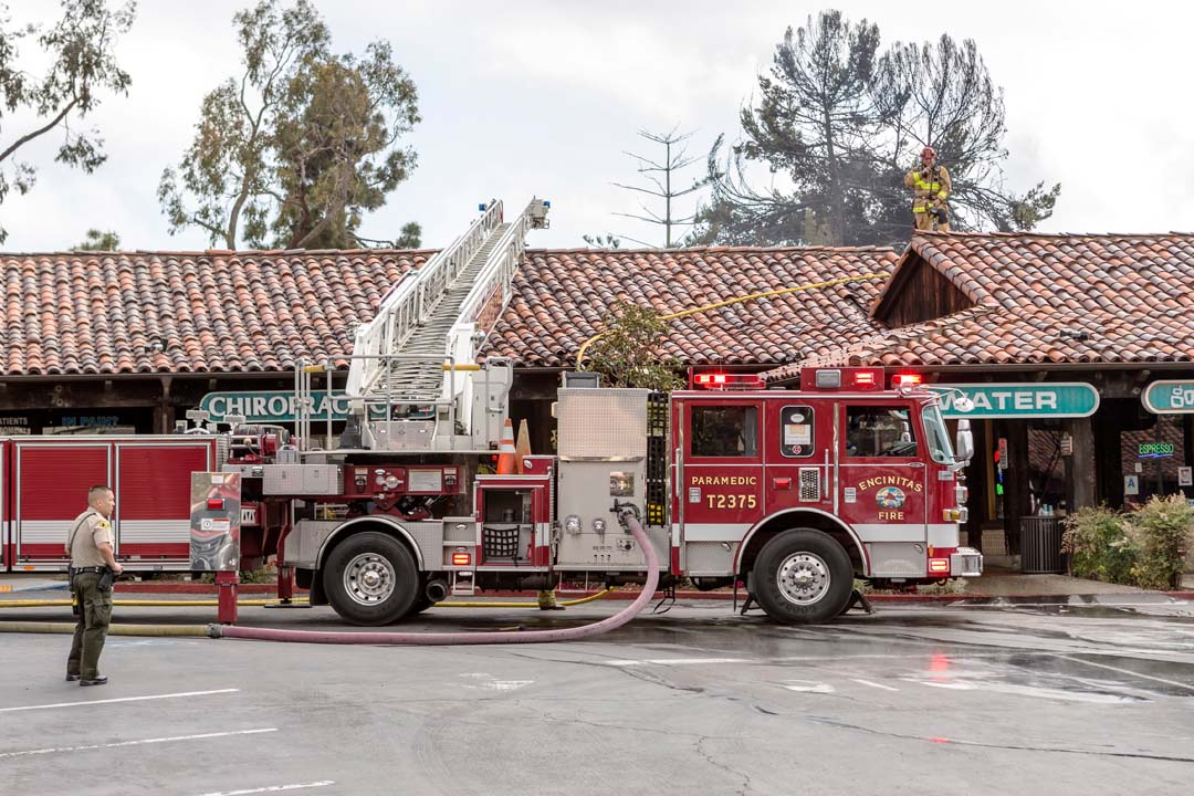 Encinitas firefighters look for hot spots on the roof of a structure located at 441 Encinitas Blvd. Photo by Bill Reilly