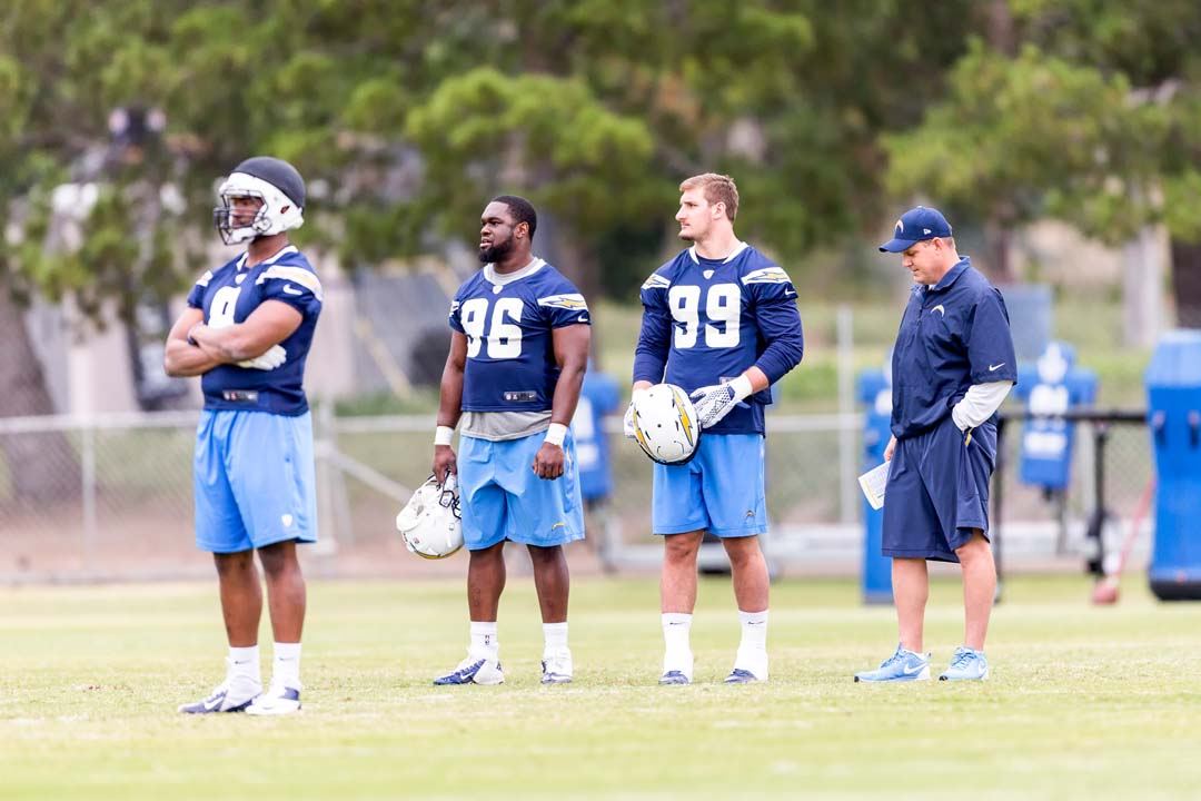 San Diego Chargers number one draft pick Joey Bosa (99) watches the offense run drills with Chuka Ndulue (96) during rookie mini-camp. Photo by Bill Reilly