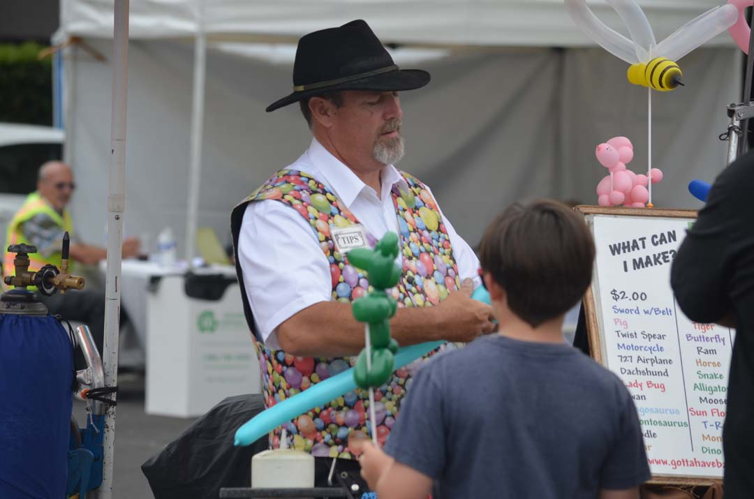 Balloon artist Steve Mings twists a balloon into a sword for a patron. Photo by Tony Cagala