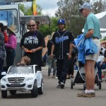 Ricky Rodriguez drives his grandson David Perez in a remote controlled Mercedes Benz down Grand Avenue. Photo by Tony Cagala