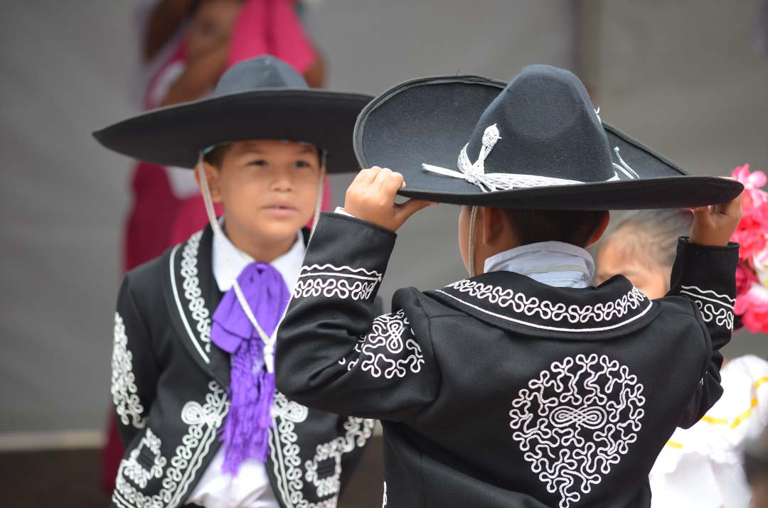 A young dancer dons his sombrero before performing. Photo by Tony Cagala