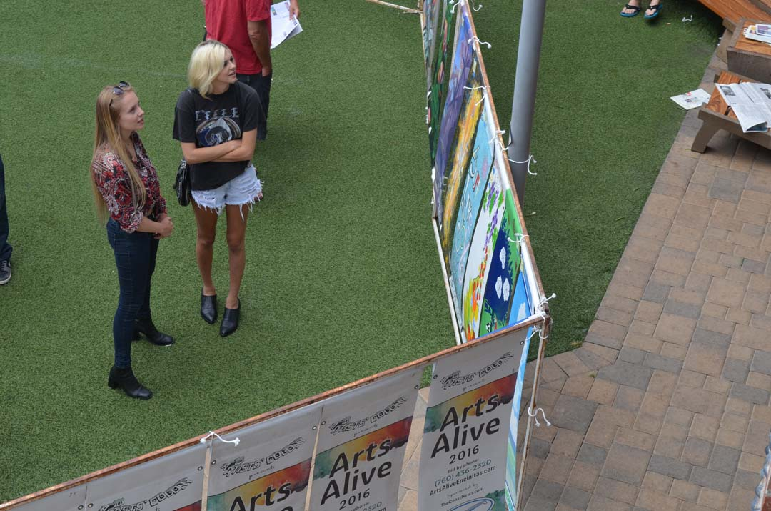 Art patrons look over the banner one last time before the live auction event begins. Photo by Tony Cagala