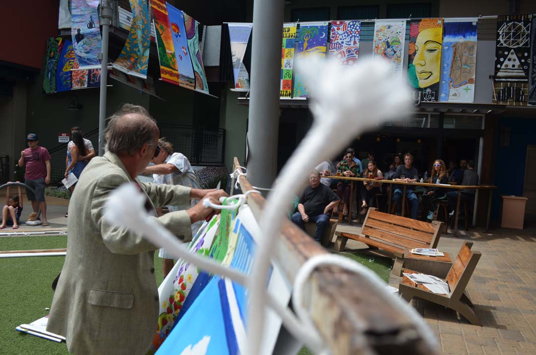 Danny Salzhandler, president of the 101 Artists' Colony, removes some of the banners for auction. Photo by Tony Cagala