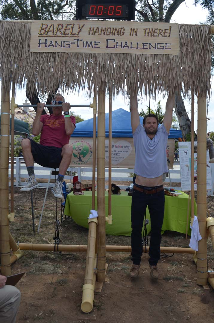 Jack Guenther, left, and Josh Braddock compete to see who can hang the longest during EcoFest Encinitas. Guenther, 69, outlasted Braddock. The exhibit was hosted by the Primate Rescue Network, a nonprofit based in San Diego aimed at rescuing primates around the world. Photo by Tony Cagala