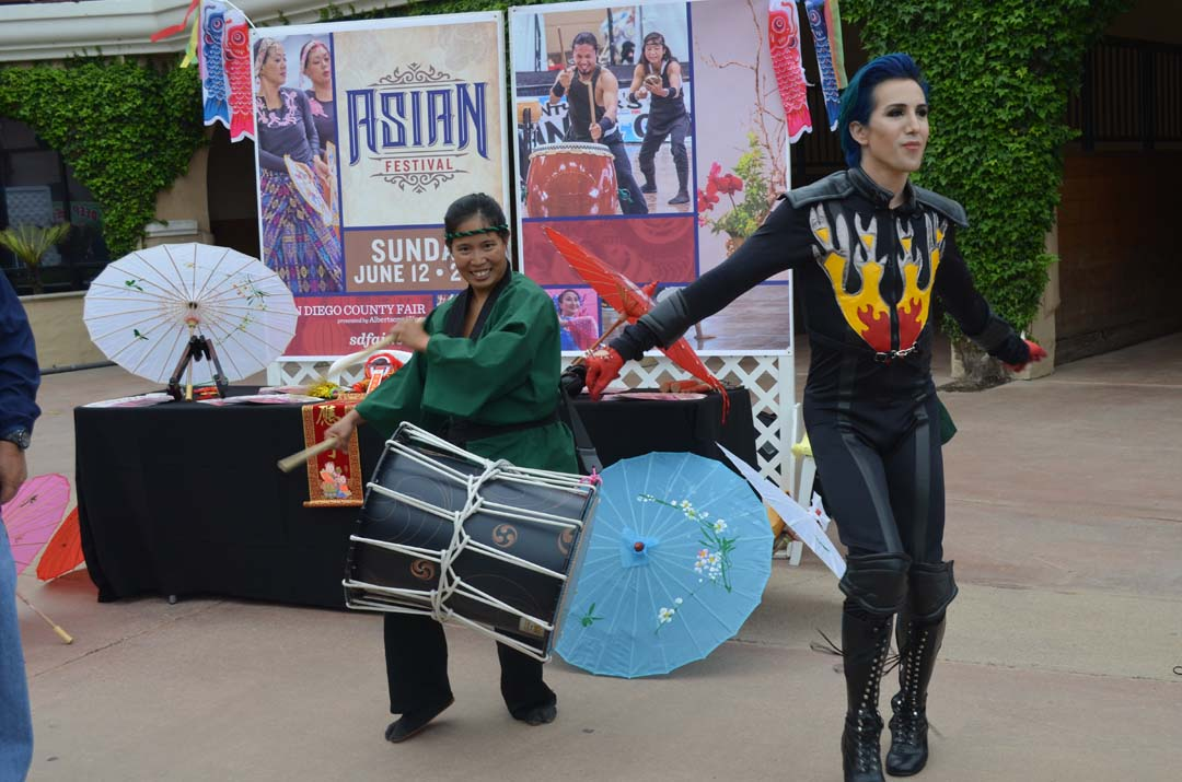 Diana Wu, left, bangs on a drum to preview Asian Festival Day June 12, while Ricky Rebel dances to the beat. Rebel will be performing at LGBT Day at the fair June 11. Photo by Tony Cagala