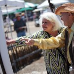 Leelah Kochan of Encinitas, receives a brief history lesson from the San Dieguito Heritage Museum's curator Dave Oakley during their Deep Pit BBQ celebration last Saturday afternoon. Photo by Pat Cubel