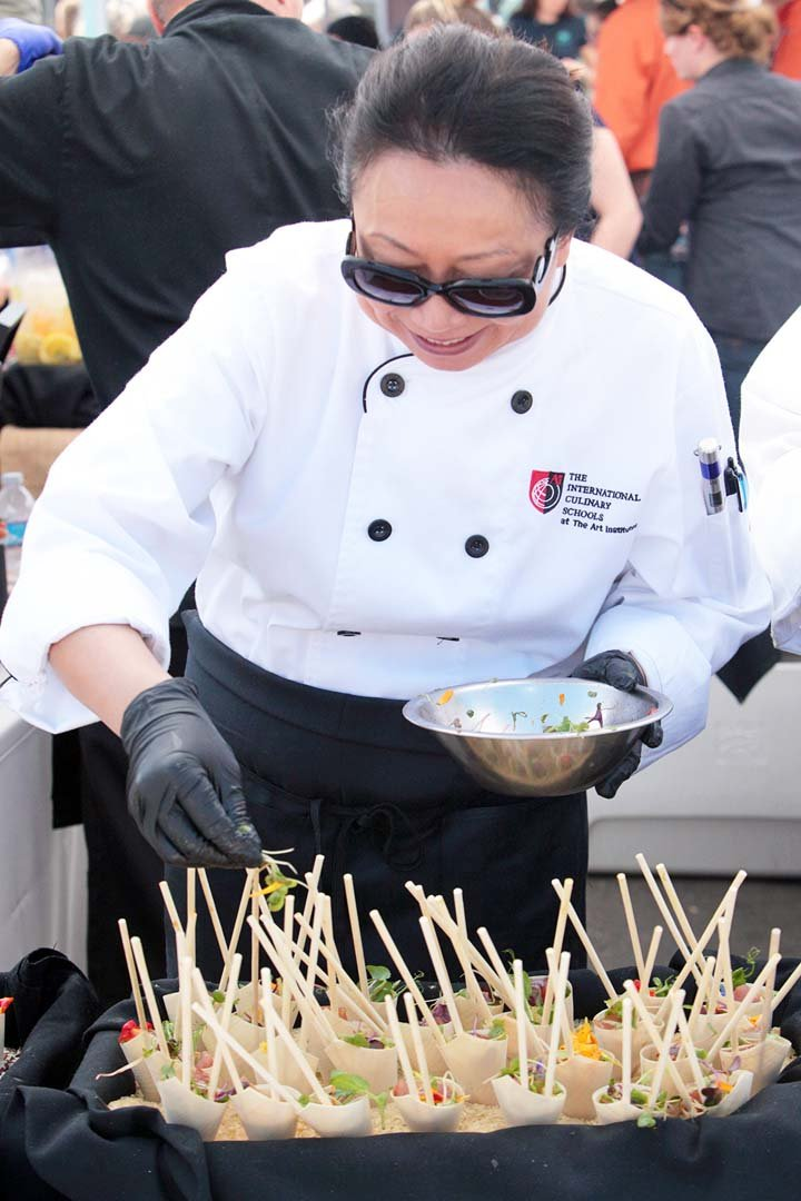 Linda Reed a culinary student preparing to graduate next month from the International Culinary School puts the finishing touches on samples served by the Bistro West restaurant during last Saturday's Foodie Fest Encinitas at the Lumberyard Plaza. Photo by Pat Cubel