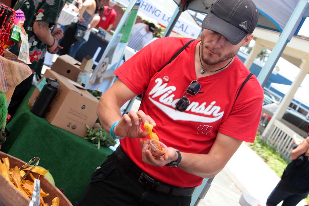 Josh Hockett samples some Odobo and plantains presented by the Q'ero restaurant at last Saturday's Foodie Fest Encinitas. Photo by Pat Cubel