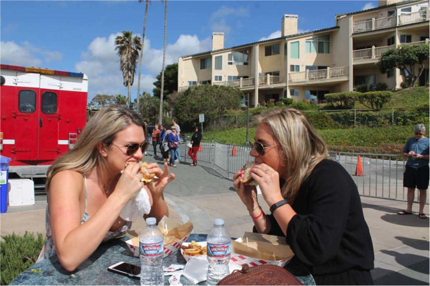 Encinitas residents Aly Blon, left, and Alyse Calcagni, enjoy New York-style sandwiches from one of the many food trucks at the 37th annual Fiesta Del Sol.  Photo by Alex Hansen