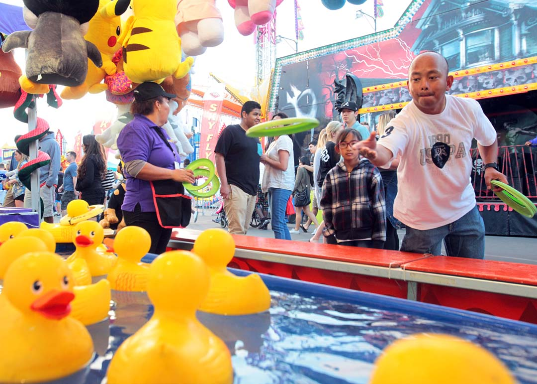A fairgoer attempts to win a prize at a ring toss game stand. Photo by Pat Cubel