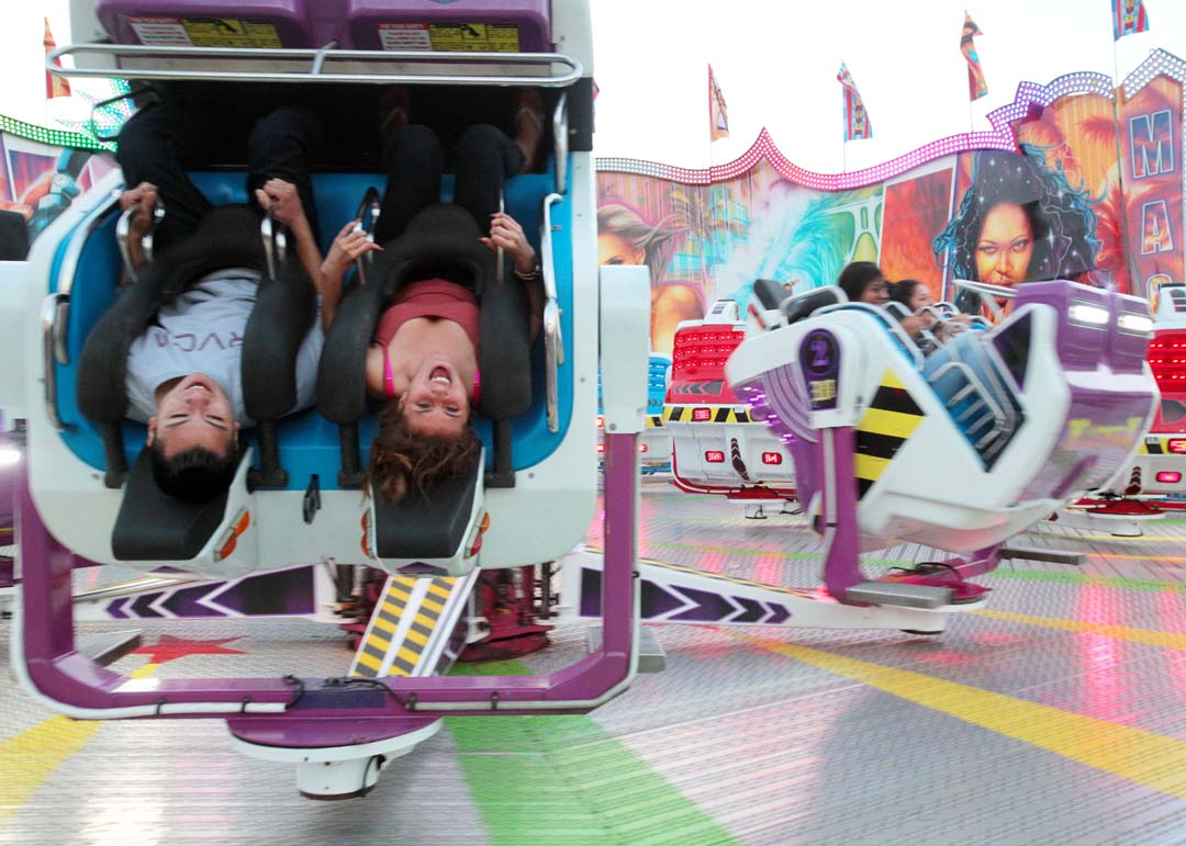 Fairgoers go upside down on a ride at the San Diego County Fair on Opening Day. Photo by Pat Cubel