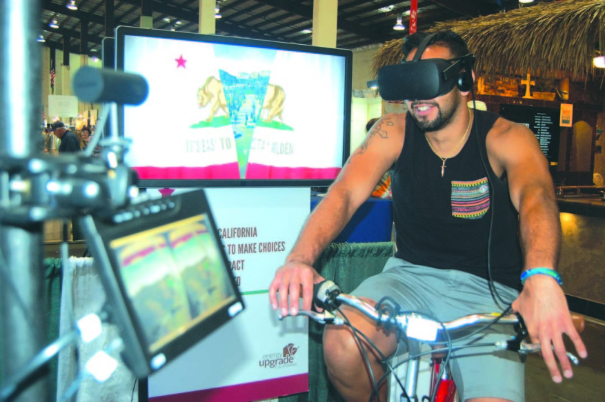 San Diego resident Jose Esquivel learns about his environmental choices while taking a virtual reality bike tour of California at the San Diego County Fair.  Photo by Bianca Kaplanek