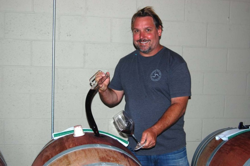 Carruth Cellars owner Adam Carruth samples his 2014 North Coast Bordeaux at a barrel tasting during the June 11 grand opening of his expanded Cedros Avenue facility.  Photo by Bianca Kaplanek