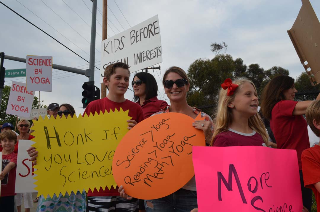 From left: Brady Small, Robin Small and Kate Small take part in a protest outside of the Encinitas Union School District office. Photo by Tony Cagala