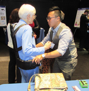 Jun Lu, right, a student at the University of California, San Diego, demonstrates a device aimed at protecting seniors when they fall on during Saturday's Design Competition Showcase. Photo by Steve Puterski