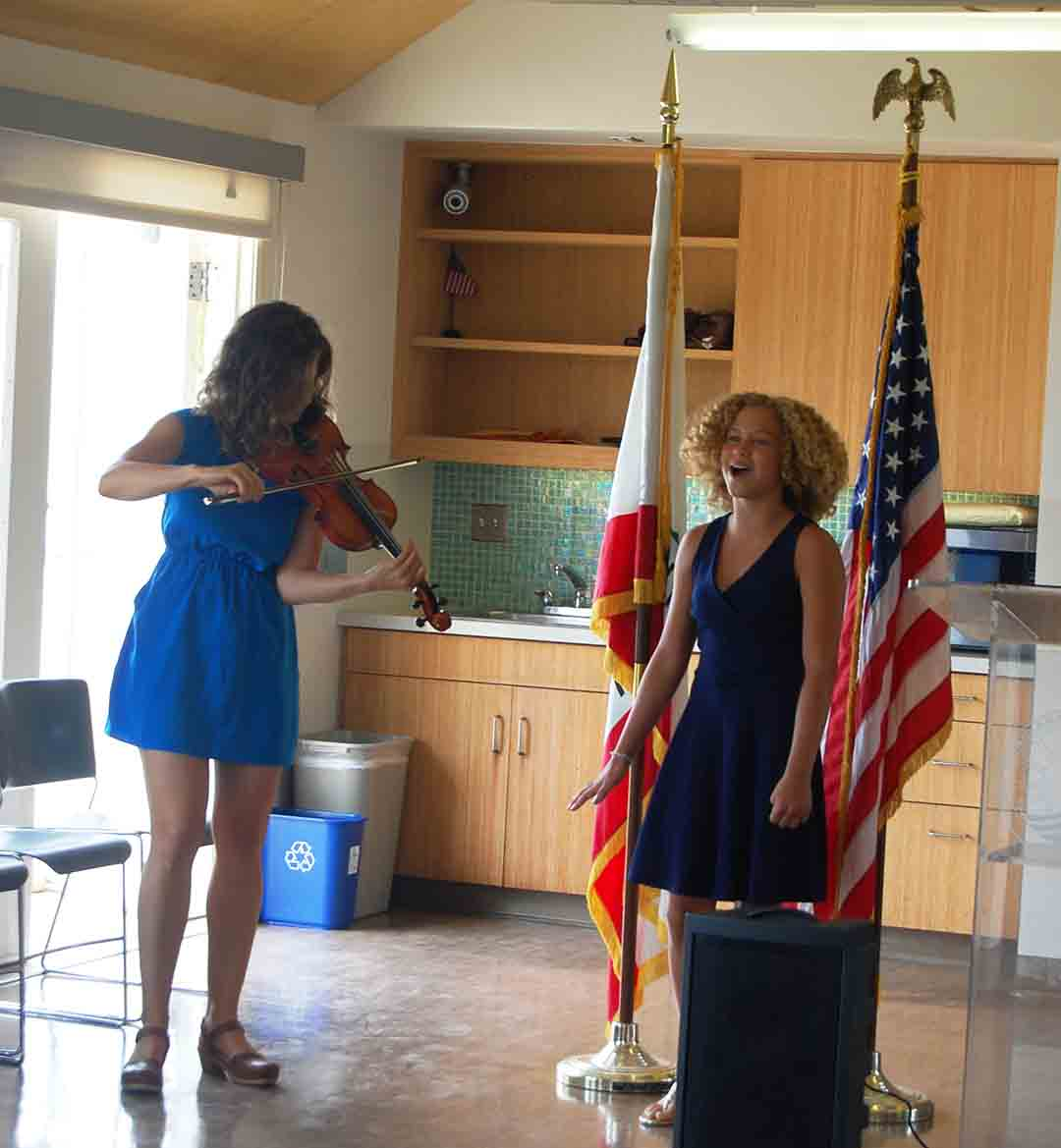 """Marguerite Ostro plays the violin as Lexi Worms sings """"Solana Beach, Our City Proud,"""" the city song."""