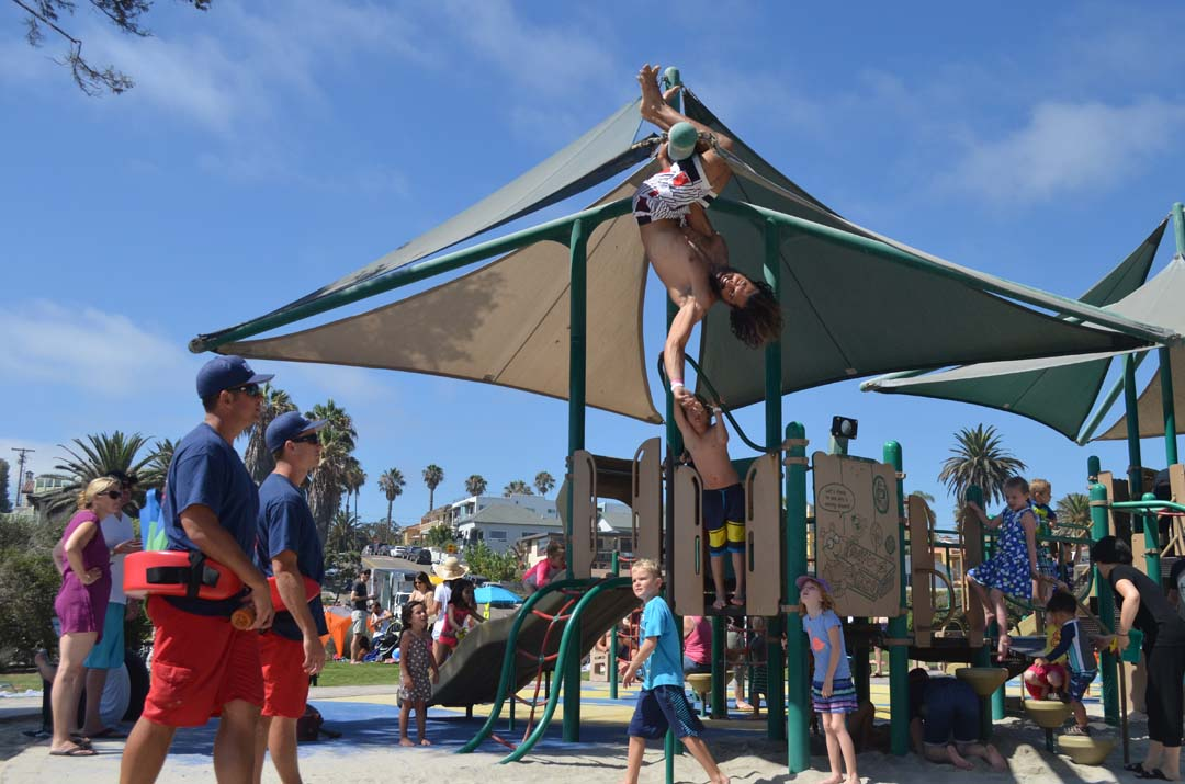 Encinitas lifeguards try to coral a man hanging from the playground equipment. Photo by Tony Cagala