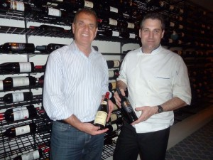 Parc Bistro-Brasserie Owner Garo Minassian, left, and new Executive Chef Donald Lockhart display fine wines at the new Bankers Hill San Diego location. Photo by Frank Mangio