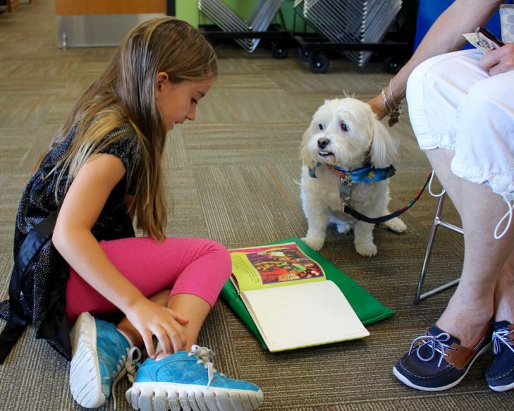 Amelia Hislop, 7, of Oceanside, reads to Baron. Photo by               Promise Yee