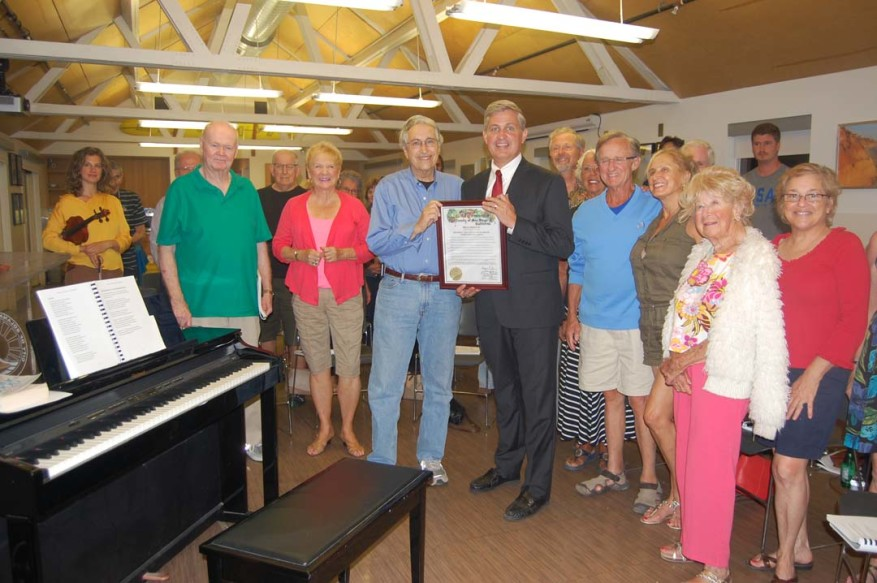 More than two dozen people are on hand as the Solana Beach sing-along entered its 30th year. Supervisor Dave Roberts, center right, presented a proclamation declaring Aug. 11, 2016, City of Solana Beach Community Sing-Along Day throughout the county to event founder Ed Siegel, center left. Photo by Bianca Kaplanek