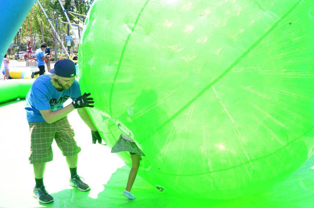 A youngster gets some help entering a human hamster wheel. Photo by Tony Cagala