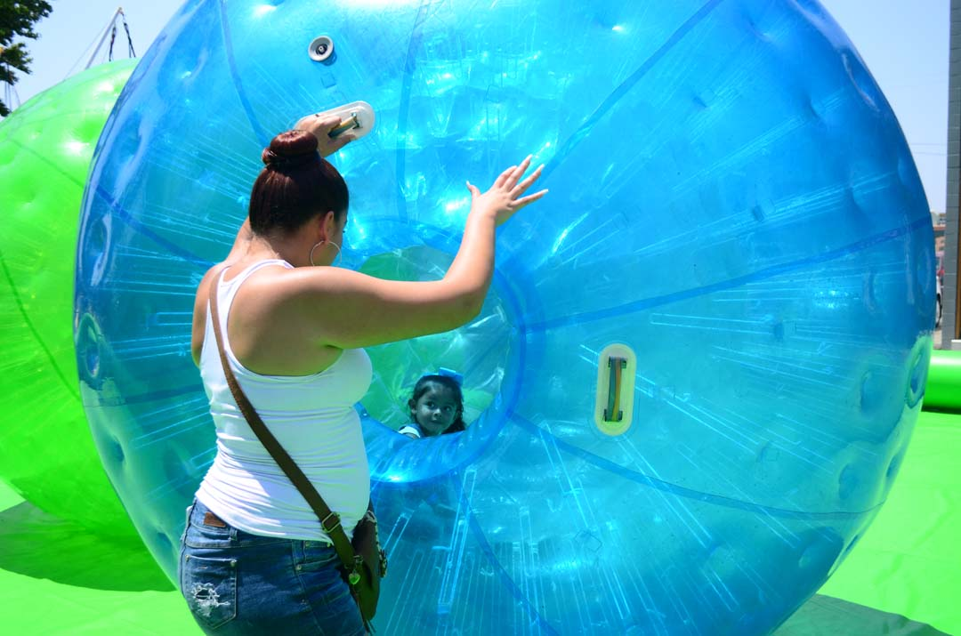 A young girl gets some reassurances from her mom before rolling around in a human hamster wheel. Photo by Tony Cagala