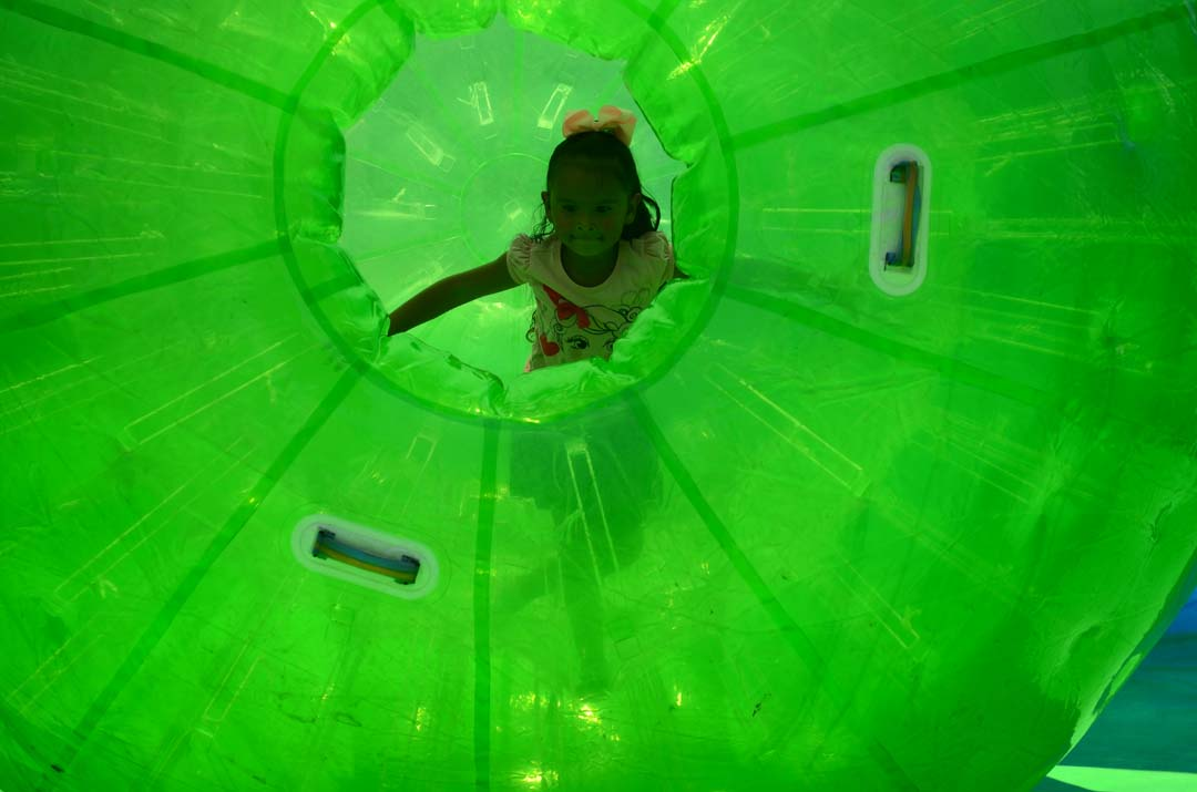 A girl rolls around in a human hamster wheel. Photo by Tony Cagala
