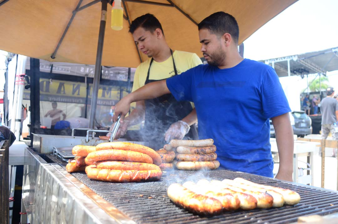 Grillers tend to sausages from Gourmet Sausages Grill on Saturday. Photo by Tony Cagala