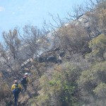 Two CalFire firefighters make their way up a hillside to examine a hot spot. Photo by Tony Cagala
