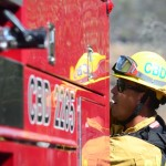 A Carlsbad firefighter grabs equipment from a truck. Photo by Tony Cagala