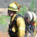 A firefighter from the Carlsbad Fire Department receives some instruction before heading down to help lay more hose lines. Photo by Tony Cagala