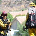 Firefighters with the Carlsbad Fire Department begin making their way down into a brushy area. Photo by Tony Cagala