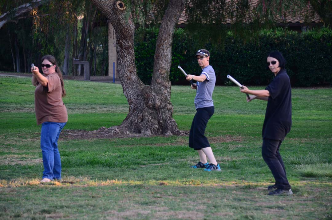 """Genevieve Edge, center, leads Heidi Pyka, left, and Jay Hall, right, through some choreography during a Lightsaber Team, Escondido chapter, meet up in Kit Carson Park. The group meets every Friday to train, typically with lightsabers, in """"Star Wars""""-themed choreography.  Photo by Tony Cagala"""