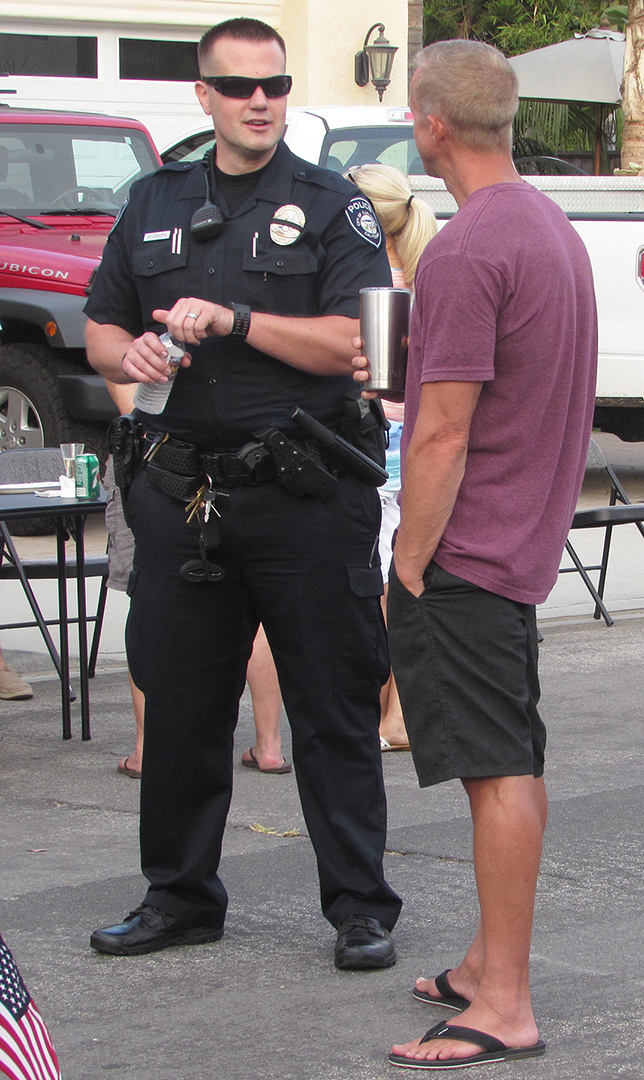 A Carlsbad police officer speaks with a resident on James Drive on Tuesday as part of National Night Out. Photo by Steve Puterski