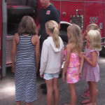 Carlsbad firefighter Brandon Birse shows off a group of girls Tuesday in support of police officers during National Night Out. Photo by Steve Puterski