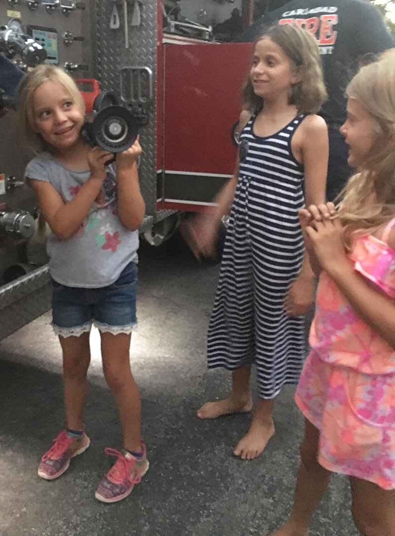 Kinsey Genewich, left, holds a fire hose Tuesday during National Night Out as friends Mollie Shields, middle, and Ella DesAutels look on. Photo by Steve Puterski