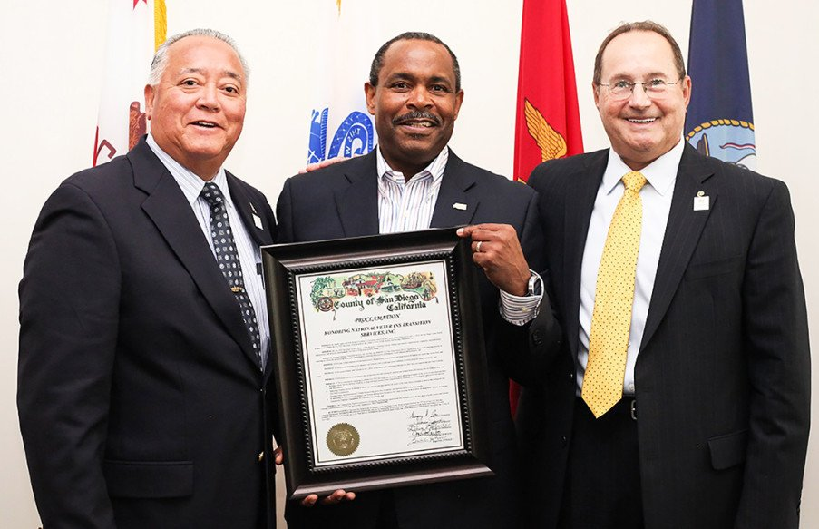 Wilfred Quintong, left, and Timothy Matheus, right, present retired Navy Master Chief Maurice Wilson with a Live Well San Diego proclamation on July 29 in Escondido. Courtesy photo