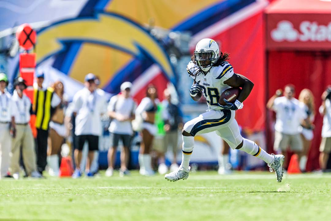 San Diego Chargers running back Melvin Gordon (28) looks down field as he runs the ball against the Jacksonville Jaguars defense. Photo by Bill Reilly